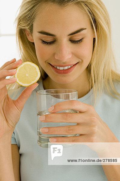 Frau mit Wasserglas und Zitronenscheibe