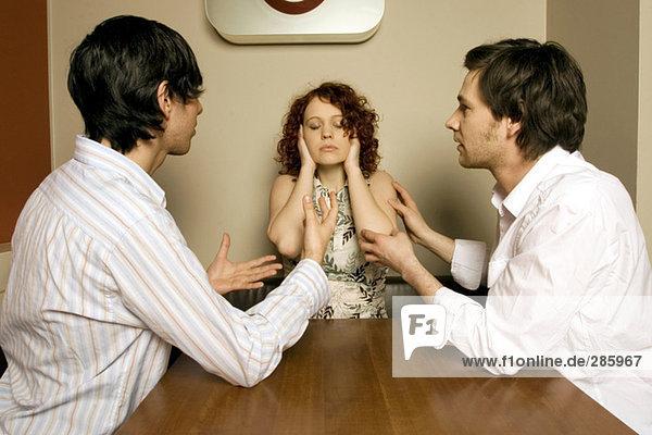 Two men looking at women shutting ears
