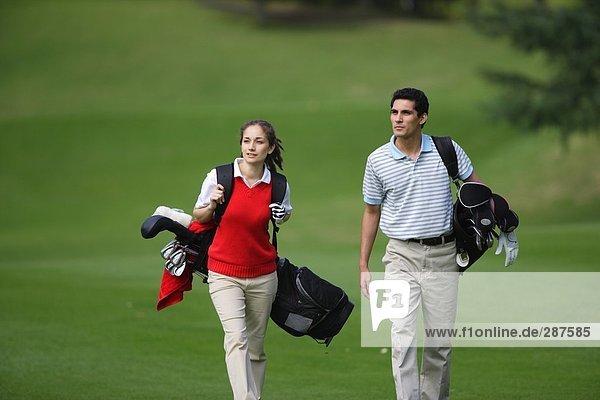 Seitenansicht einer ein paar Wandern auf dem Fairway  wie sie ihre Golfbeutel tragen