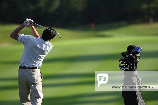 Männlichen Golfspieler schlagen in Richtung des grünes