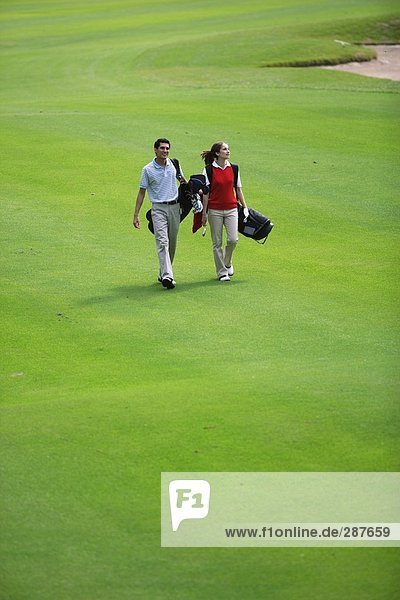 Paar geht hinunter Wiederschiffbarmachung der ein Golfplatz