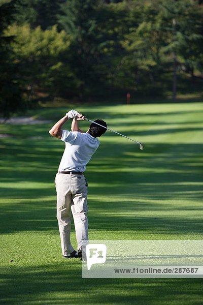 Männlich Golfer einen Golfschläger geschwungen