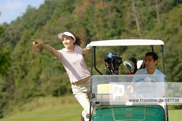 Eine Frau weist die Richtung ihrer Golf-partner