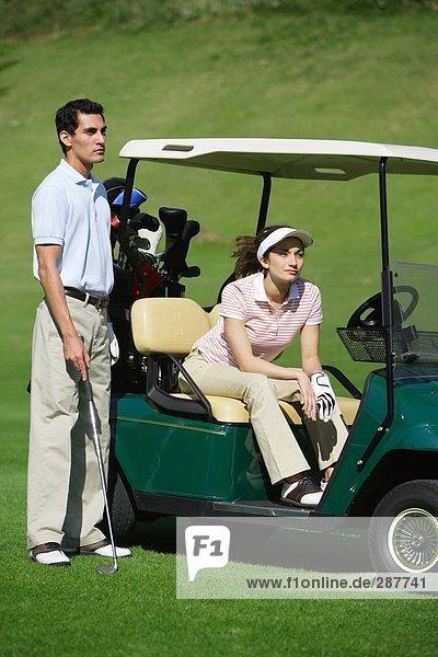 Seitenansicht einer Frau sitzen in einem Golf-Cart als Mann steht neben ihr