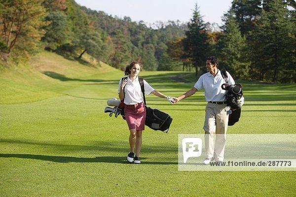 Paar hält hände wie sie gehen hinunter den fairway