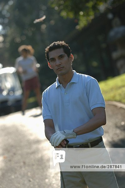 Man posing in front of the camera holding a golf club