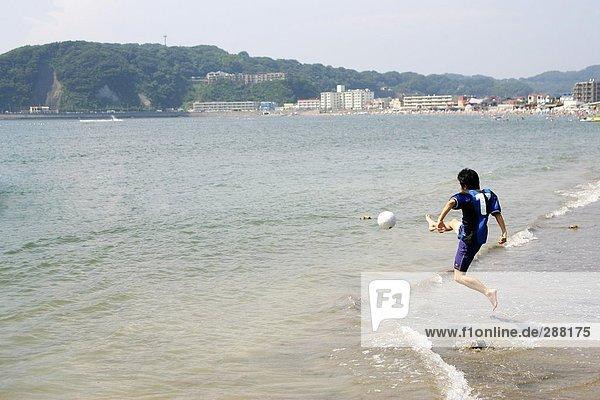 Junger Mann spielen Fußball am Strand