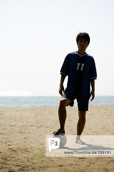 Silhouette eines jungen Mannes mit einem Fußball am Strand