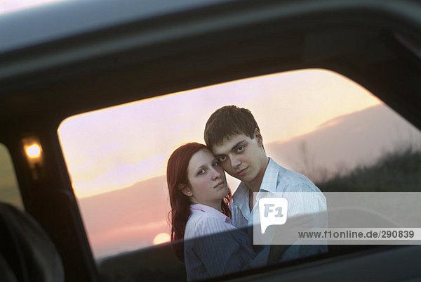 Porträt jungen Paares in Umarmung gesehen durch Autofenster
