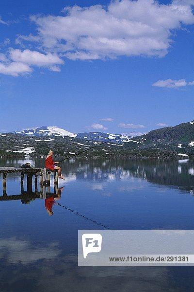 Eine Frau Angeln von einer Brücke durch einen ruhigen See in den Bergen.