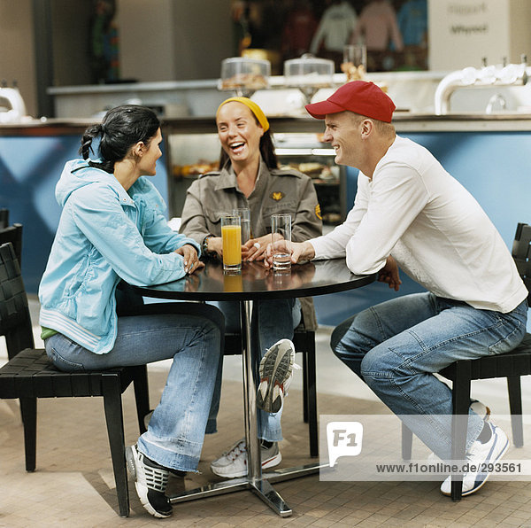 Three people in a cafe.