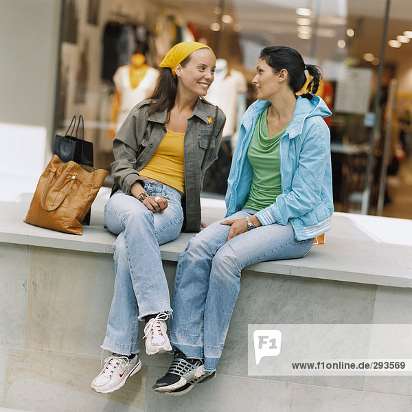 Two smiling women sitting in front of a shop-window.