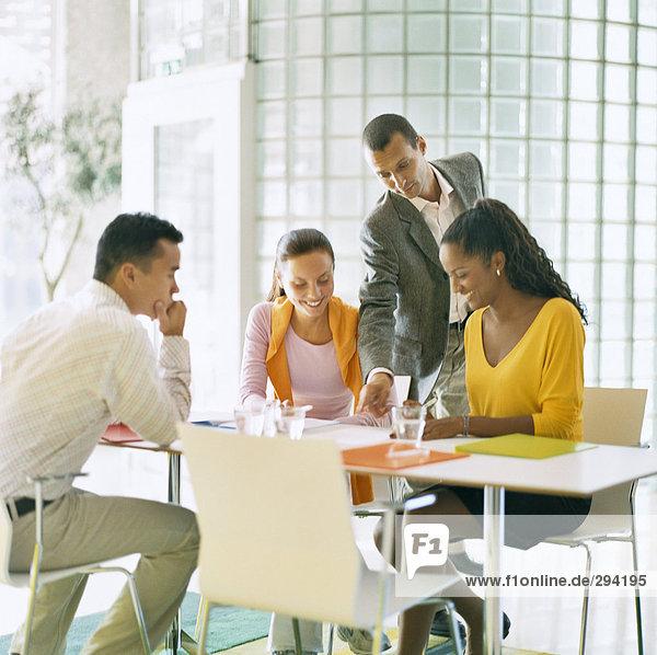 Zwei Frauen und zwei Männer  die ein Treffen in einer Büroumgebung.