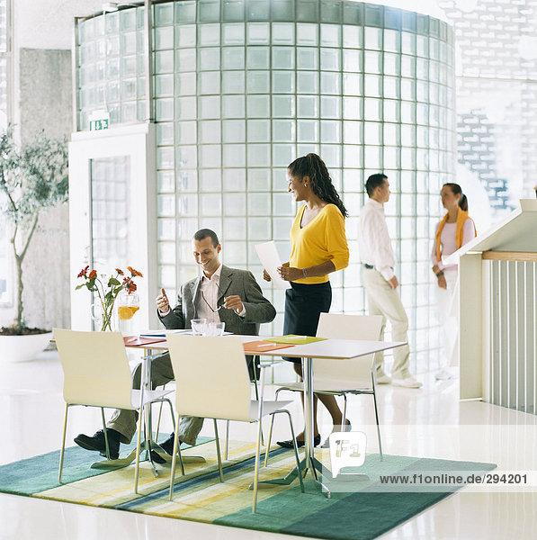 Ein Mann sitzend von einer Tabelle im Gespräch mit einer Frau steht hinter ihm und eine Frau und ein Mann in den Hintergrund Office-Umgebung.