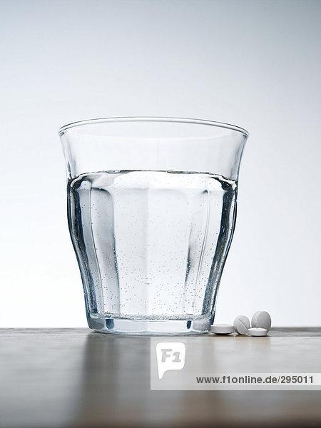 Pillen und ein Glas Wasser.