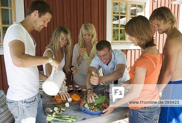Eine Gruppe von Menschen im freien Essen zubereiten.