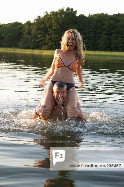 Ein Mann in das Wasser führenden eine Frau auf seinen Schultern.