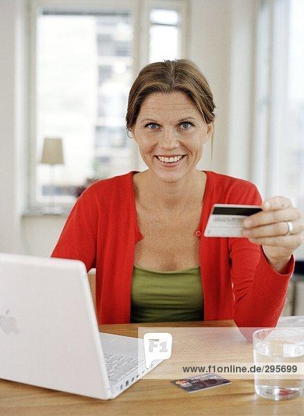 Eine Frau mit einer Kreditkarte von einem Computer.