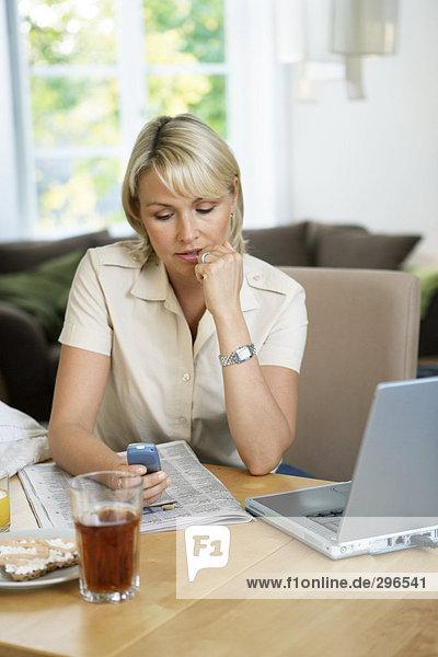 Eine Frau sitzen an einem Tisch mit einem Mobiltelefon.