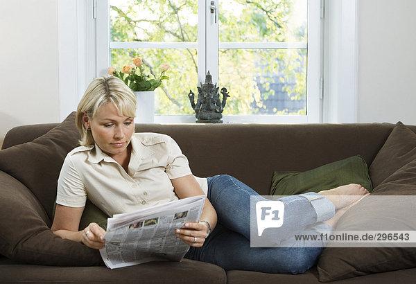 Eine Frau ein Papier in einem Sofa lesen.
