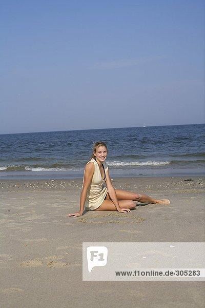 Junge Frau sitzt am Strand - Urlaub - Einsamkeit  fully_released
