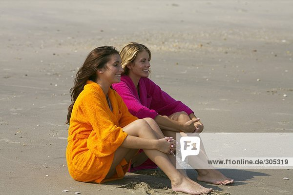 Two young women in bathrobes sitting at the beach