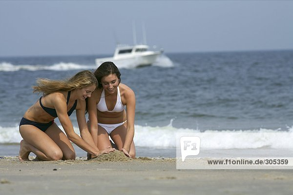 Zwei junge Frauen im Bikini bauen etwas aus Sand - Freundinnen - Urlaub  fully_released