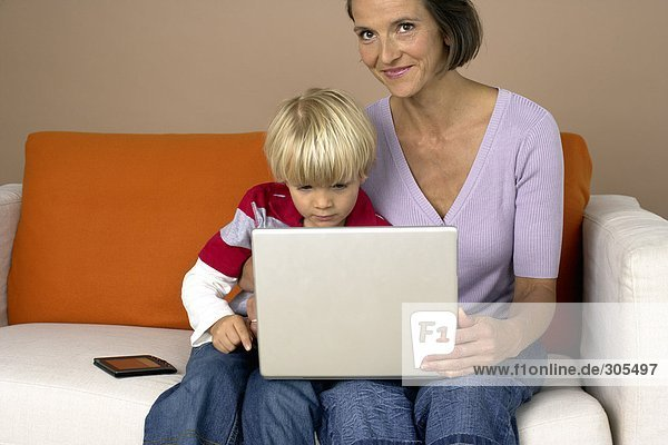 Mutter und Sohn sitzen mit einem Laptop auf dem Sofa  fully_released