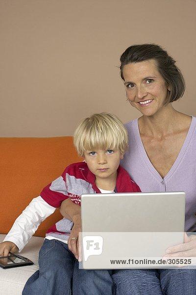 Mutter und Sohn sitzen vor einem Laptop  fully_released
