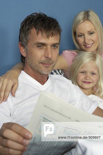 Mann liest Börsenzeitung mit Frau und Tochter im Bett - Familie - Harmonie  fully_released