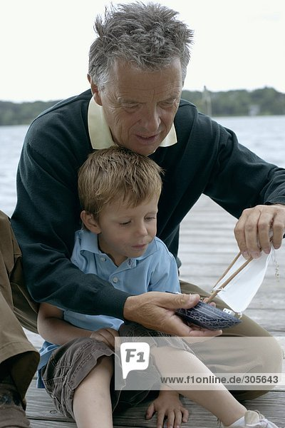 Gray-haired man with a boy in front of him is repairing a boat  selective focus