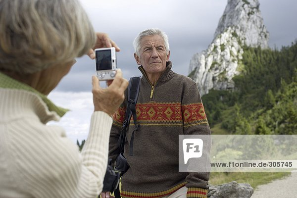 Senior adult woman taking a picture of her husband in the mountains  selective focus