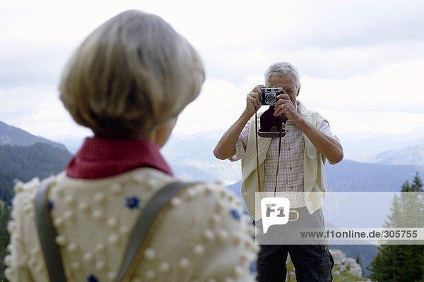 Weißhaariger Mann fotografiert seine Frau in den Bergen - Landschaft - Ausflug  fully_released