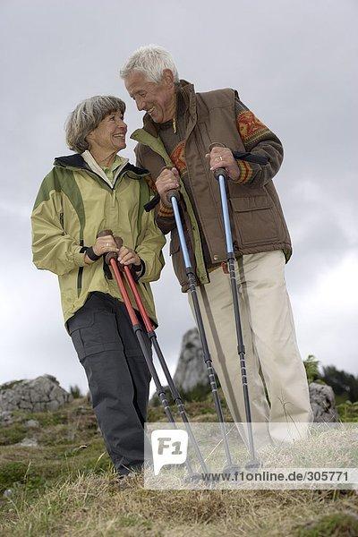 Älteres Ehepaar mit Wanderstöcken in den Bergen - Freizeit  fully_released