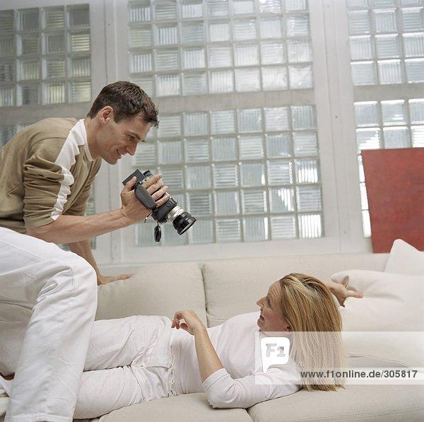 Mann filmt eine blonde Frau auf dem Sofa - Paar - Hobby - Wohnzimmer