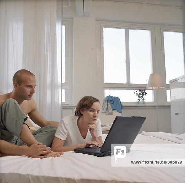 Junge Frau liegt im Bett und arbeitet mit einem Laptop neben einem jungen Mann - Morgens - Technologie