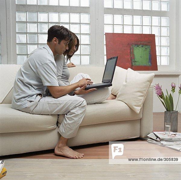 Frau und braunhaariger Mann schauen auf einen Laptop - Sofa - Wohnzimmer - Home