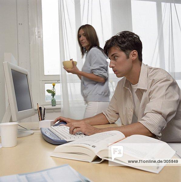 Junger Mann arbeitet an einem Computer während seine Freundin frühstückt - Studium