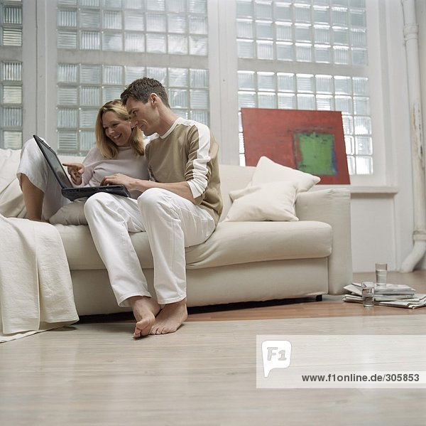 Blonde Frau und braunhaariger Mann schauen auf einen Laptop - Sofa - Wohnzimmer - Home