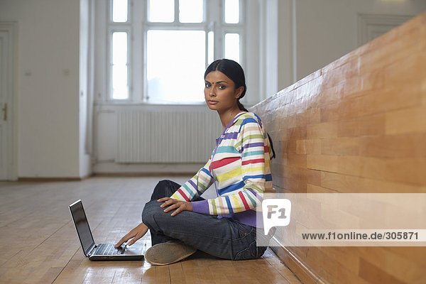 Junge indische Frau sitzt in einem Hörsaal vor einem Laptop auf dem Boden - Studium - Brauch