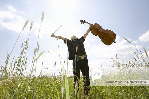 Junger Mann im Feld stehend mit Cello  Tiefblick