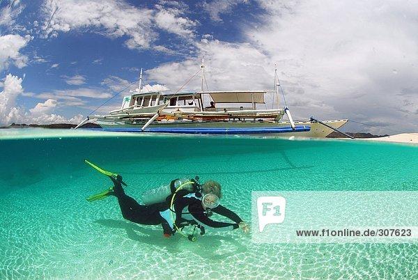 Philippinen  Dalmakya Island  Taucherin im Meer  Unterwasseransicht