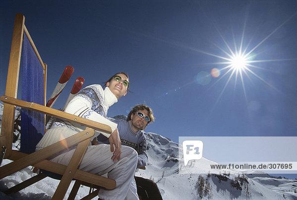 Paar auf Liegestühlen im Schnee sitzend  Blickwinkel niedrig
