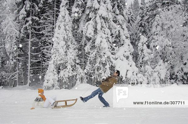 Paar mit Schlitten mit Spaß im Schnee