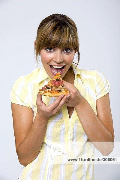 Junge Frau isst Pizzastückchen  lächelnd