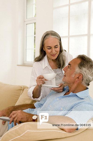 Erwachsenes Paar im Wohnzimmer  Frau hält Tasse  Nahaufnahme