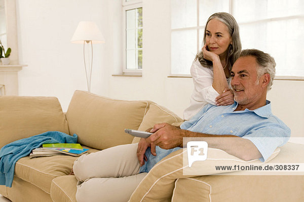 Mature couple in living room  man using remote control