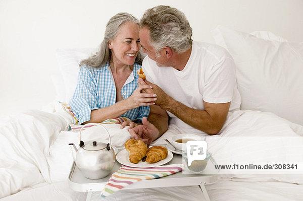 Erwachsenes Paar auf dem Bett sitzend mit Frühstück  lächelnd