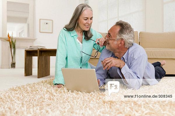 Erwachsenes Paar auf Teppich mit Laptop liegend  lächelnd