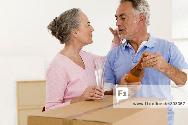 Erwachsenes Paar mit Champagnerflasche und Glas  Nahaufnahme